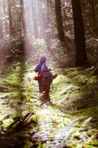 2 Kinder stapfen im Sonnenstrahl durch den Wald