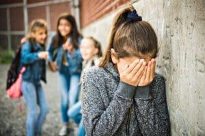 Mädchen hält sich die Augen zu - hinter ihrem Rücken wird gelästert