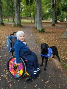 Nora (ein Mädchen im Rollstuhl) und Zoe (ein Assistenzhund)