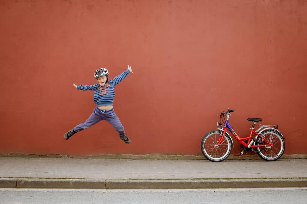 Kind springt vor roter Wand