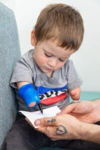 armamputierter Junge mit Malhilfe der Firma Pohlig