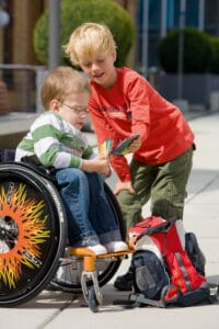 Zwei Kinder, eins im Rollstuhl