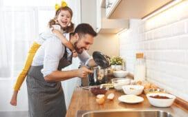 Mann mit Kind auf dem Rücken kocht