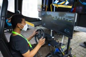 Jugendlicher sitzt mit Maske vor einem Fahrsimulator