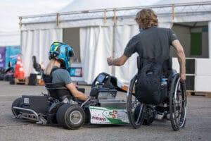 Rollstuhlfahrer neben GoKart