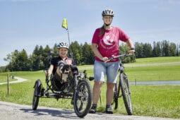 Mädchen auf einem Kettwiesel neben einer Radfahrerin
