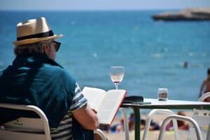 Mann liest am Strand sitzend ein Buch