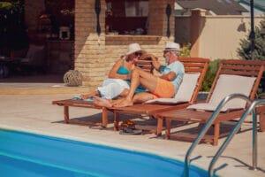 Paar auf Liegestühlen am Pool